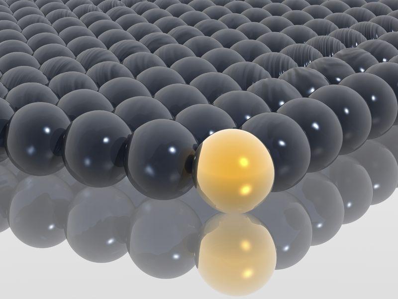 Yellow sphere leading black balls